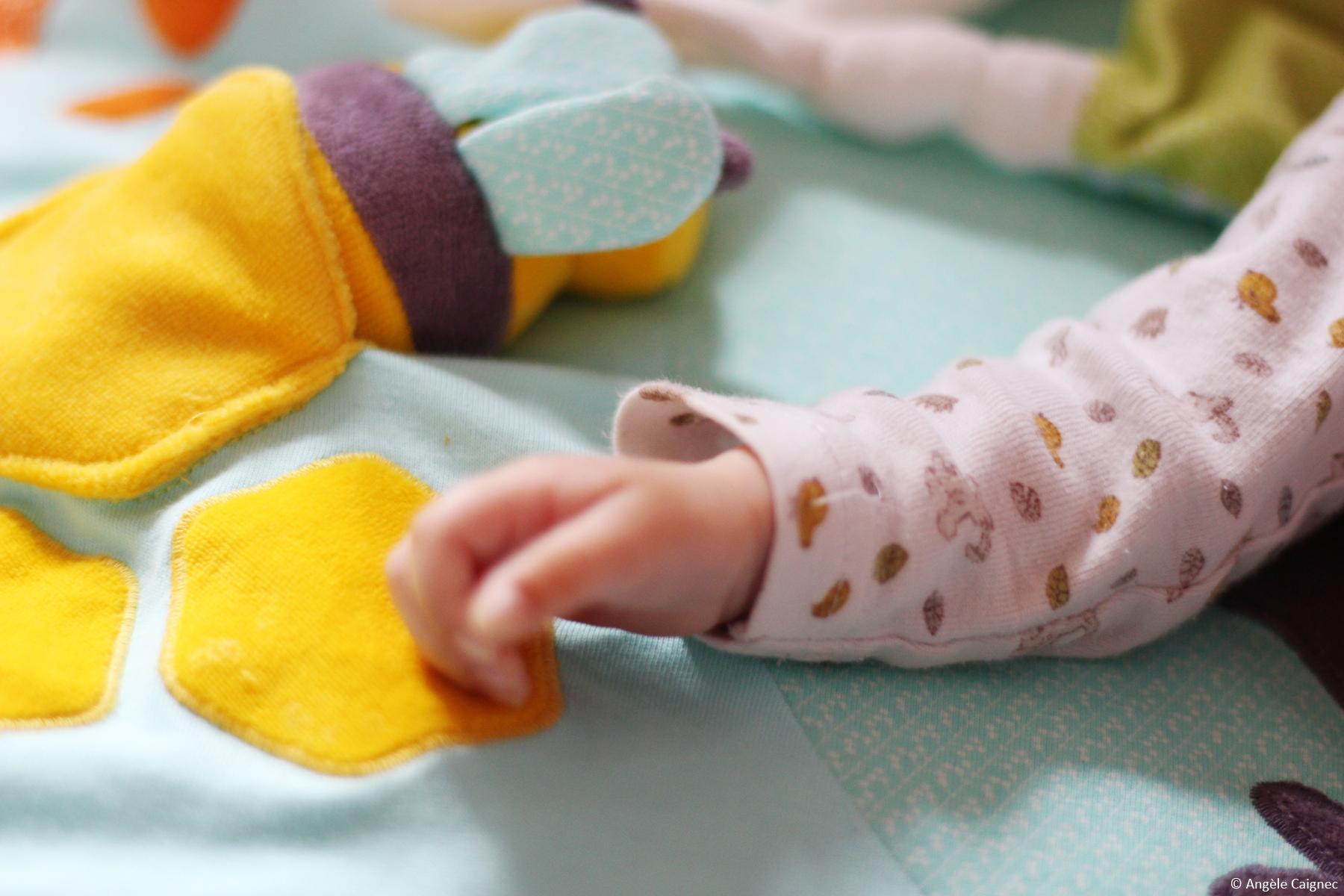 Détail de la main de mon bébé sur son tapis d'éveil