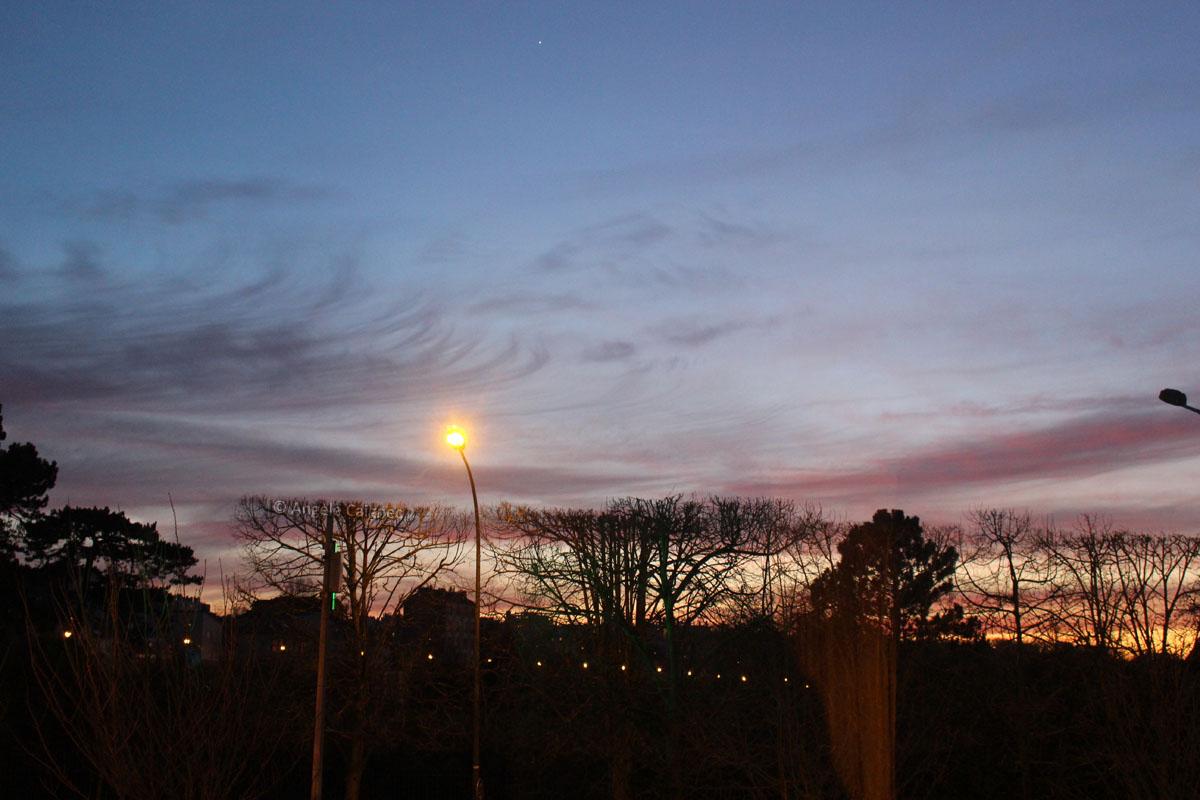 Ciel de coucher de soleil orienté ouest, couleurs bleu et traces de nuages violacés sur fond jaune