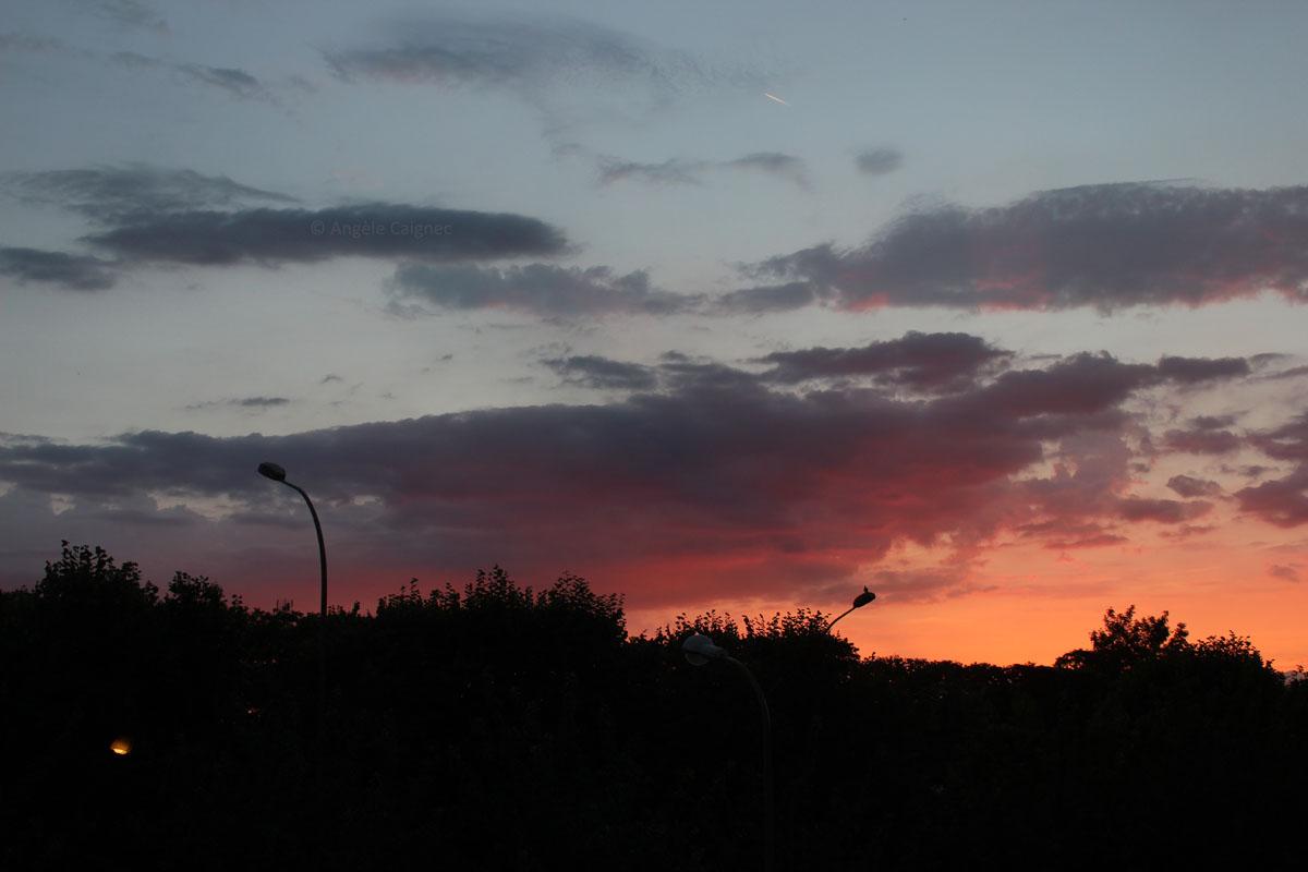 Ciel de coucher de soleil orienté ouest, ciel bleu gris et orange du soleil couchant avec d'épais nuages aux couleurs sombres violet foncé, gris et rosé