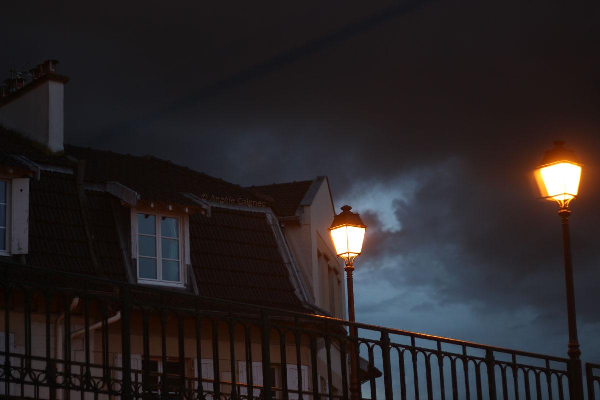 lampadaires allumés sous un ciel orageux en soirée à Saint-Cloud