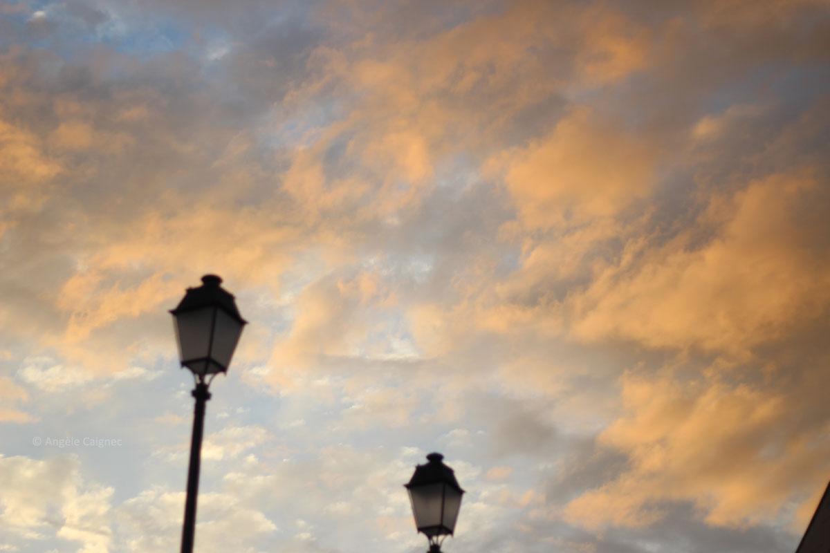 Ciel de fin d'après-midi, comme une peinture impressionniste, jetée de nuages grisés aspergés d'éclats jaunes du soleil bas, fond bleu clair
